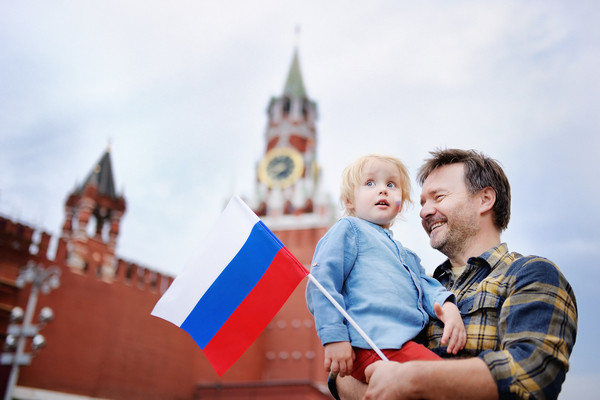 Man holding a baby and Russian flag near the Kremlin
